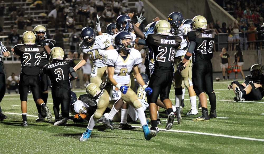 The+Akins+varsity+football+offense+celebrates+after+a+last+minute+touchdown+to+take+the+lead.+The+Eagle%27s+finished+the+game+with+a+26-23+season+opener+victory+over+the+Crockett+Cougars.+