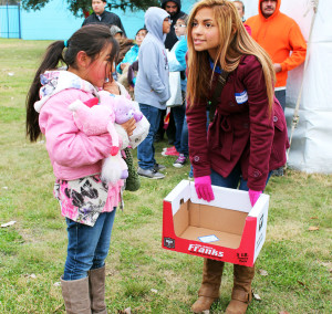 "Senior Adrianna Moreno assists a girl with directions at the The River City Youth Foundation Annual Merry Memories. ""It's good for students to volunteer, because it makes you a more humble,and appreciative person,"" Moreno said. Kids approached Akins Key Club volunteers all morning long to ask for directions or goodie bags."
