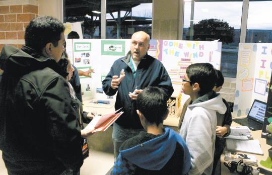 ACES teacher Eric John explains Green Tech's programs to families. Green Tech was introduced at the annual Academy Fair last week.