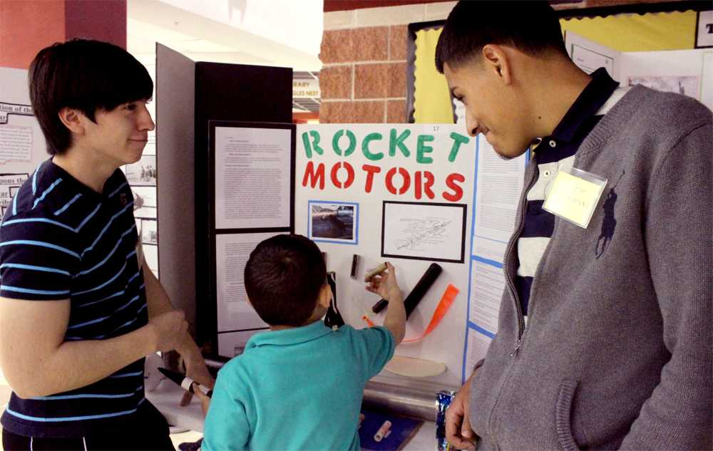 Senior Josue Gonzalez and his partner show young students their Rocket Motors science fair project. This was the first science fair in Akins history.