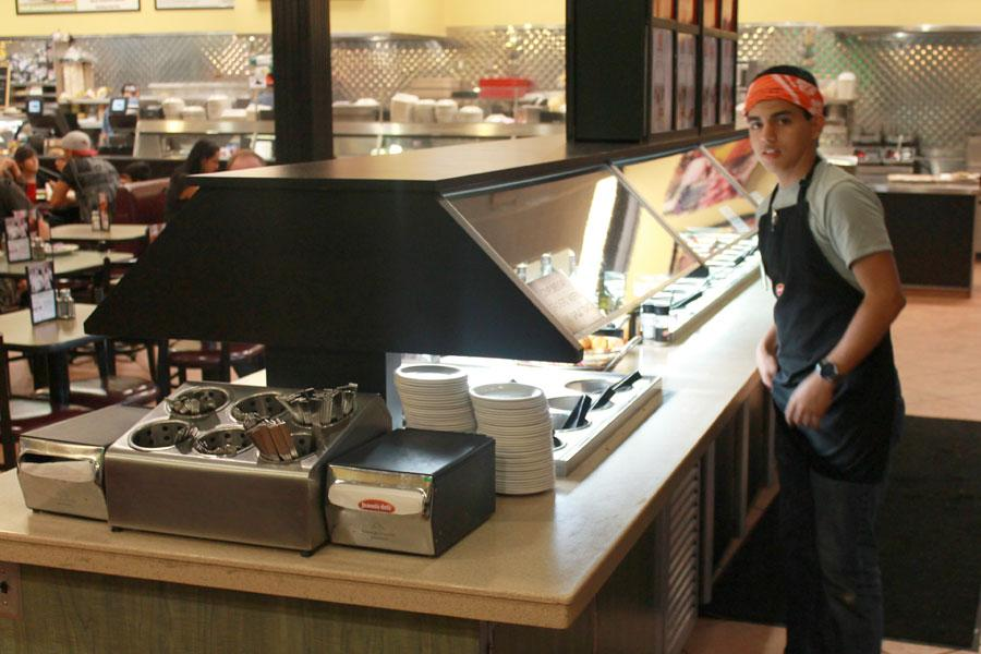 Senior Douglas Stewart cleans up the salad bar at Jason's Deli, working his late night shift.