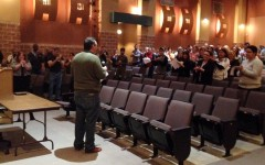 Faculty and staff give Akins High School Principal Daniel Girard a standing ovation after he announces his departure. Girard has been the principal at Akins for almost eight years.