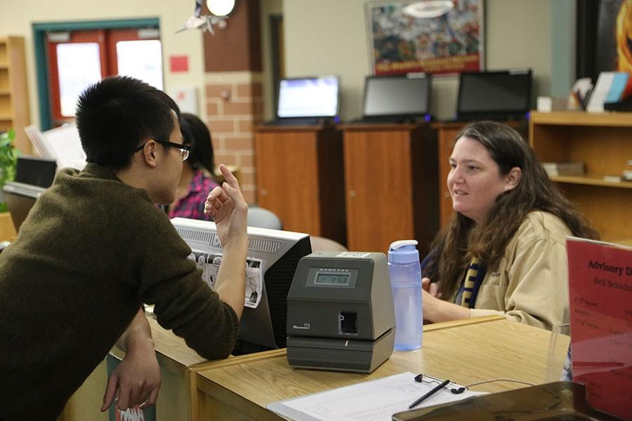 Librarian Bonnie Hauser is talking and checking out a student, one of her may tasks throughout the day.