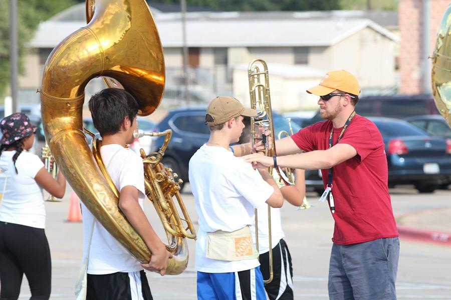 English teacher Brian Lancaster helps Brian King by adjusting his posture as he plays the trombone.