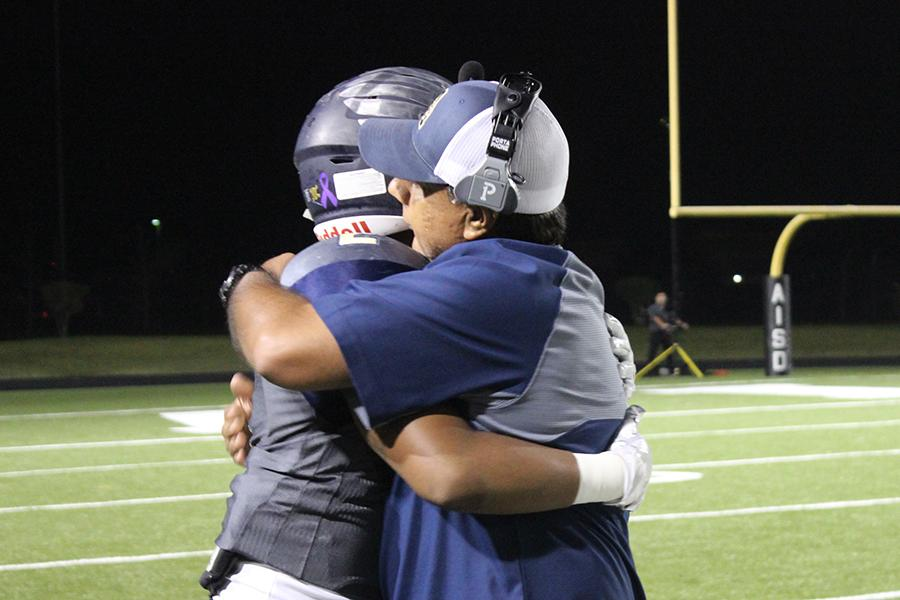 Senior running back Kenan Lockhart hugs head football Coach Humberto Garza during game against Manor, which was the last of the season.