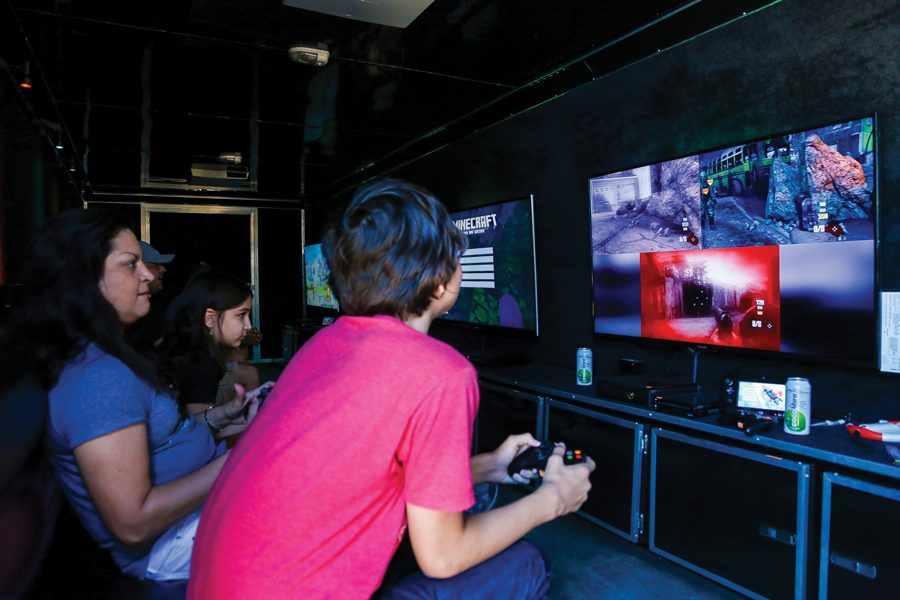 A+mother+and+her+two+children+enjoy++playing+COD+Black+OPS+2+Zombies+in+the+Rolling+Video+Games+truck.+The+truck+carries+4+TV+screens+and+holds+up+to+16+players