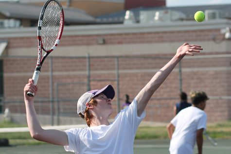 Spencer Michalke works on perfectly throwing up the ball and serving it during practice.