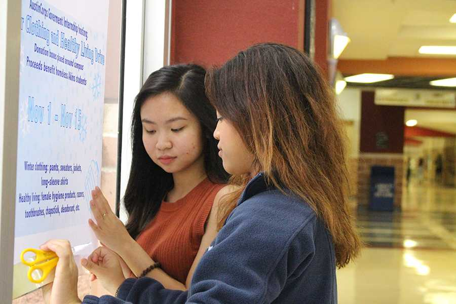 Seniors Tammy Nguyen and Yocelyn Erazo hang up posters for the Winter Clothing and Healthy Living Drive. Boxes were placed around campus with the hope of having students donate items that would help both homeless students and financially unstable students.