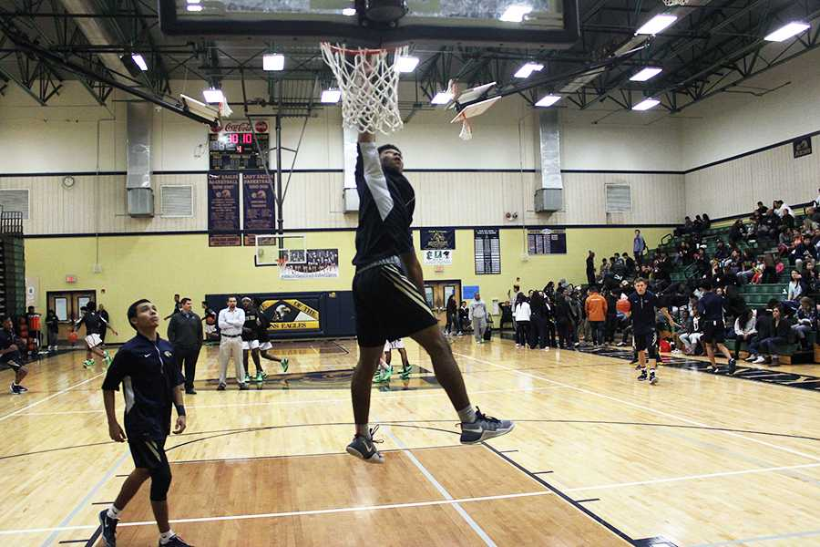Larry Durden attempts to dunk in warm ups before the Lanier High School game in December.