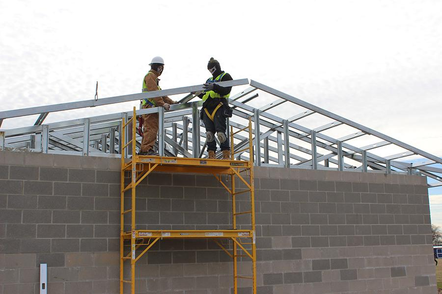 Construction workers work on building the roof on the new bathrooms and storage building on the practice field in February.