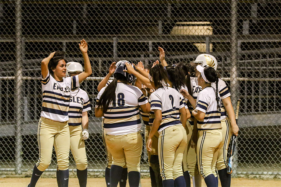 Varsity+Softball+celebrates+team+member+Sabrina+Lopez+on+her+home+run+against+Manor+on+April+4.