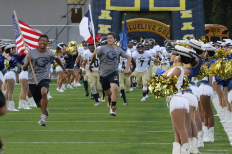 Freshman players leads the varsity Football team onto the field September 8th, during the game against Austin High.