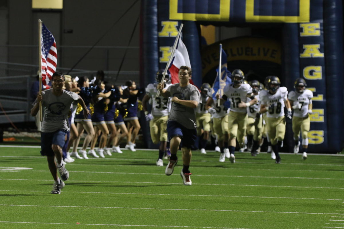 Varsity Football team appears onto the field September 8th, during the game against Austin High.