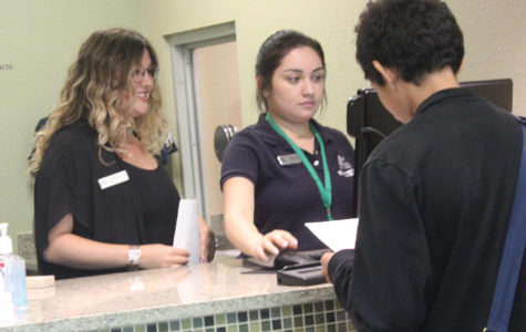 Branch manager Marla Carter and senior Mitzy Martinez work at the bank desk. Interns work after sixth period.