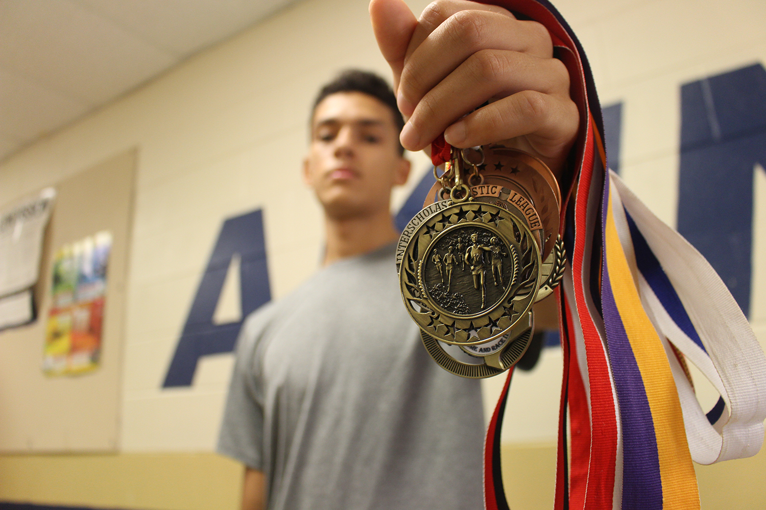 Senior Cassius Serff-Roberts shows off one of his many medals that he has won as a Cross Country runner. He beat an Akins record by running a 5K in less than 15-minutes. Later that month beating his own record with 10 seconds less than the first time.