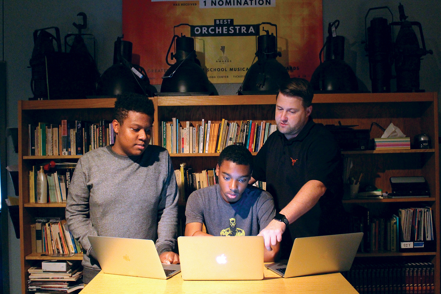 Junior Frankie Spense, freshman Chase Adkins and teacher Brad Distlehorst use new laptops to prepare for the play. It will include projection mapping software