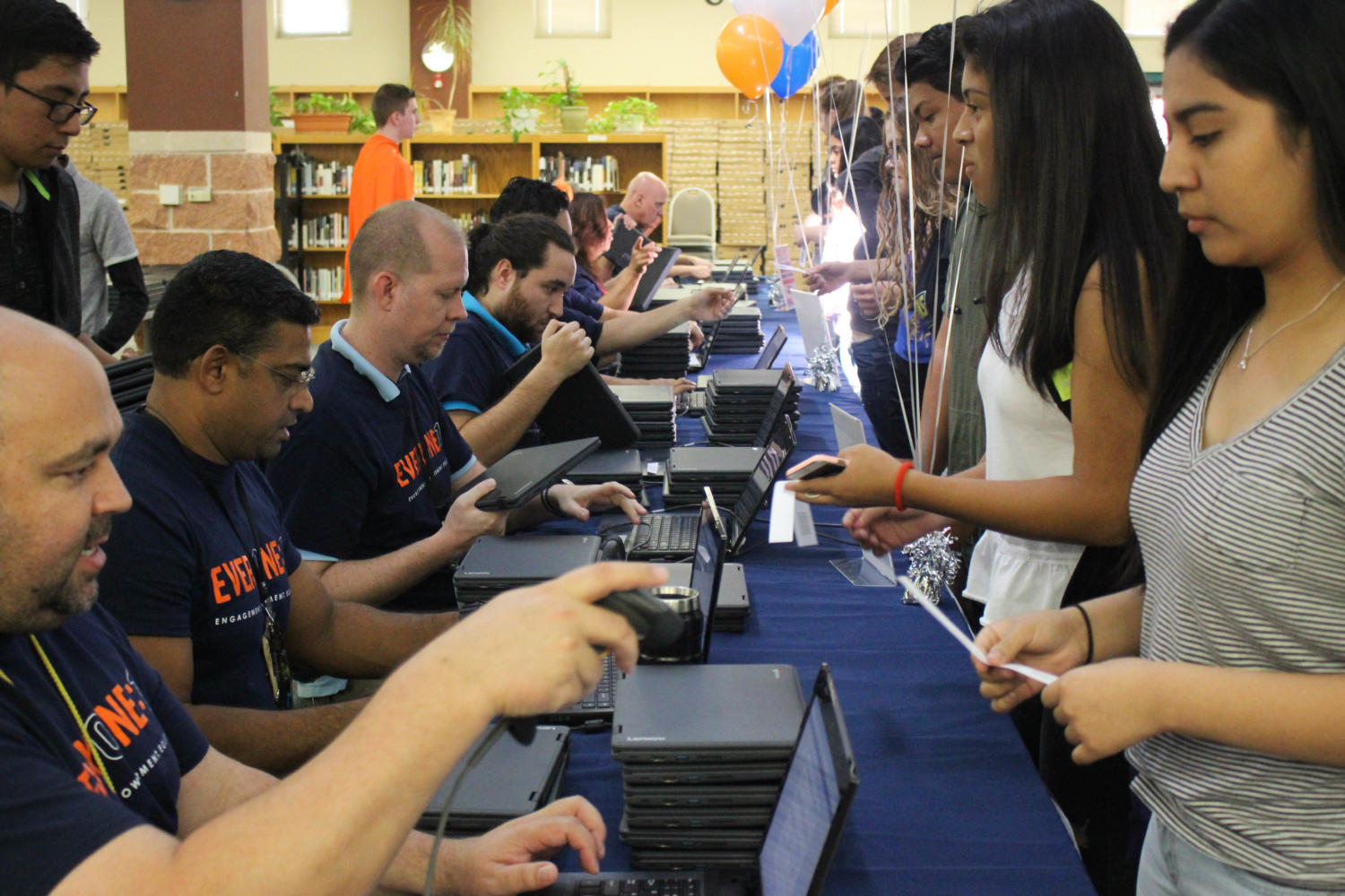 Austin ISD tech support staff and volunteers help distribute laptops to Akins students on Aug. 29 in the library. The initiative provided every student with a Chromebook that they will keep until the end of their high school career.