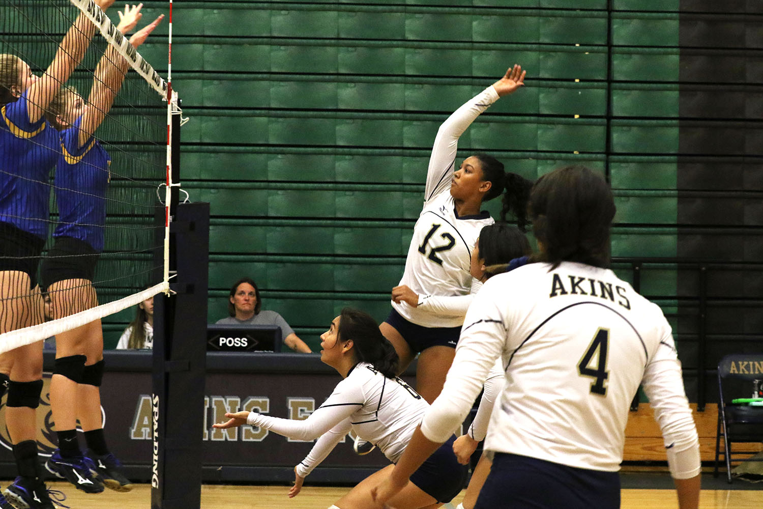 Freshman Shanti Ramdeen (12) goes for a spike as two players form the Anderson Trojans try to black it on Sept. 26. The Lady Eagles lost the game 0-3.