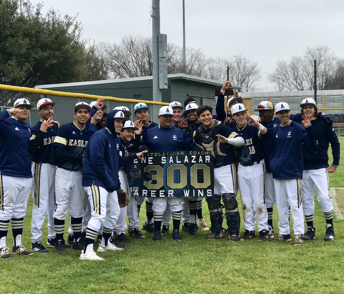 Head baseball coach Eugene Salazar and the baseball team show off a banner celebrating Salazar's 300th career win. The Varsity Baseball team defeated Leander High School 11-3, earning the distinction for Salazar.