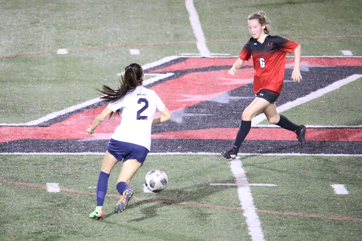 Sophomore Alex Castillo dribbles the ball on the field against their opponent Lake Travis, which defeated Akins 10-0. Coach Le'Von Griffin said he is looking for the team to make improvements that the players can make from game to game.