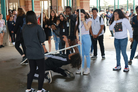 Junior Isaiah Sibi-Hackney participates in a limbo contest sponsored by Key Club  during lunch outside of the cafeteria. The contest is designed to promote the Akins-Thon fundraiser event.