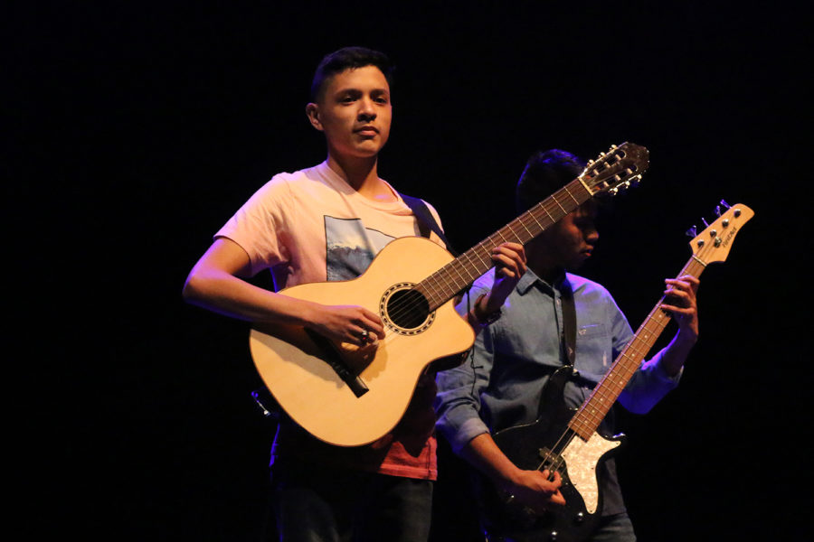 Senior Daniel plays acoustic guitar on stage.