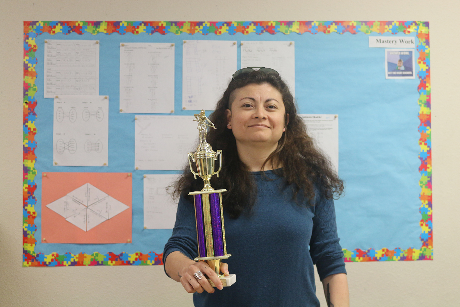 Math teacher Elise Briseno holds her APA TriCup quali cation round billiards trophy. When she isn't at school, she plays professional pool.