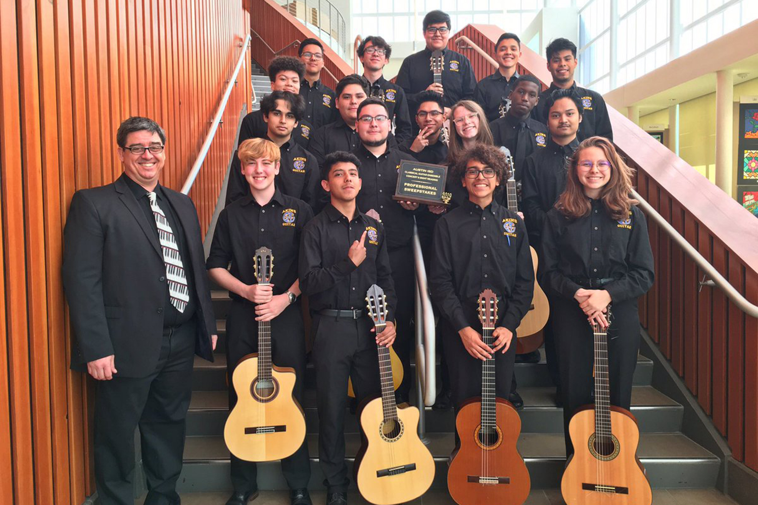 """Students in the advanced guitar class celebrate winning a """"professional sweepstakes"""" award at the University Interscholastic League's competition. Both the advanced students and the beginning students won sweepstakes in Classical Guitar Ensemble Concert and Sight Reading."""
