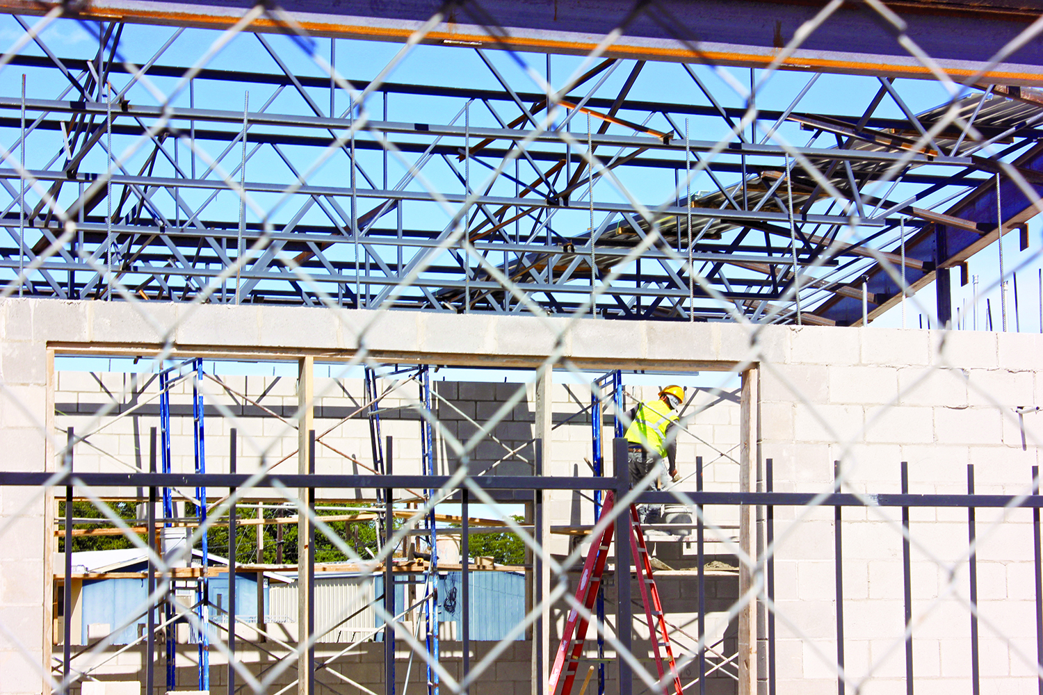 A constuction worker lifts a tub of cement onto his ladder to con- tinue laying bricks. The new weight room is expected to be done around the start of the second smemester.