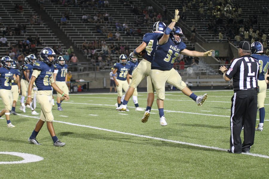 Two of our victorious varsity players celebrating after a touchdown.