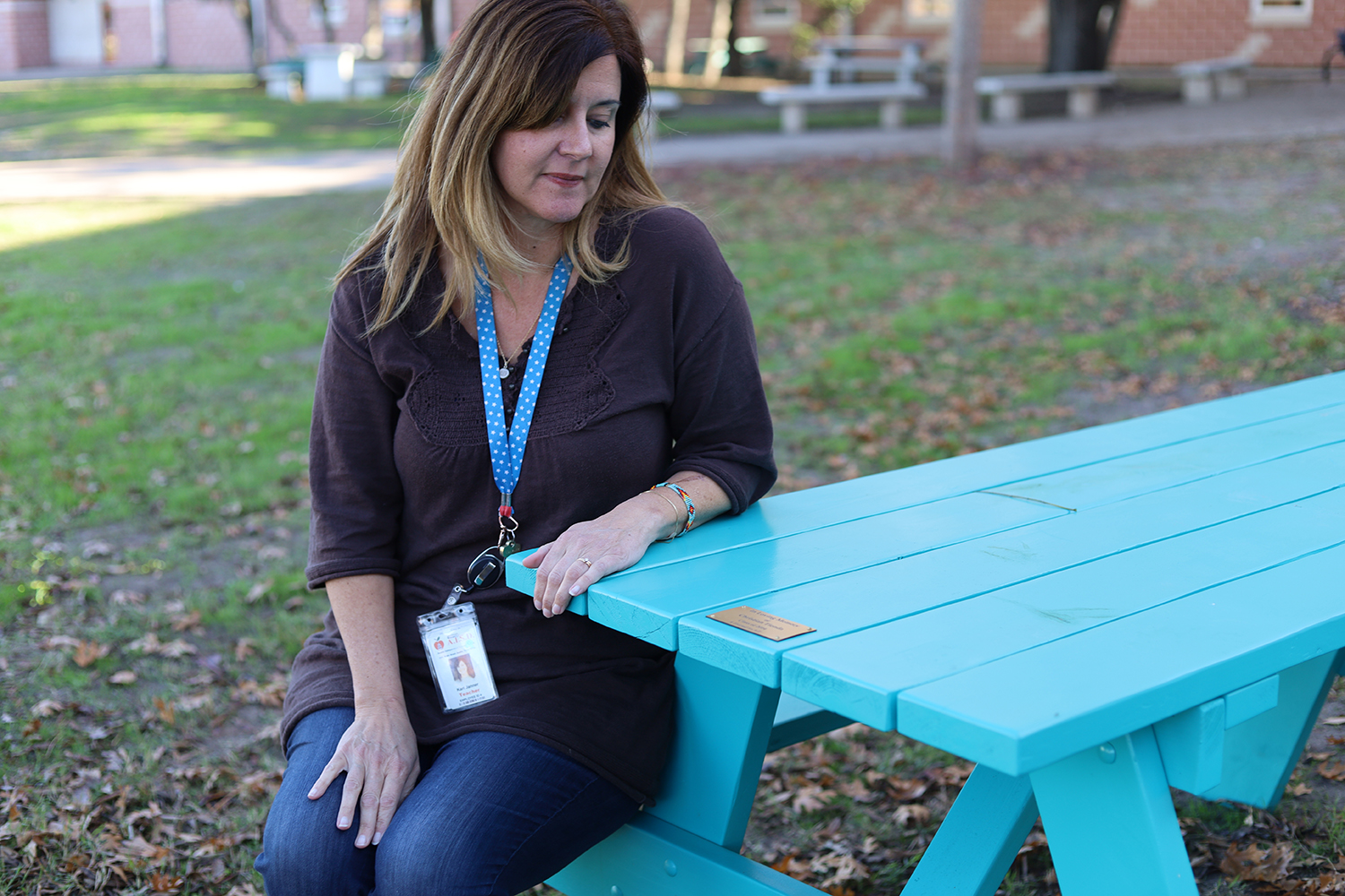 SCORES teacher Kari Janner sits at one of the two new picnic tables that were donated to the campus to honor an alum who recently passed away.