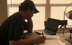Learning at the kitchen table-   Senior Andrew Hernandez does his school work at home. Hernandez said he often loses motivation to keep up with his classes while at home.