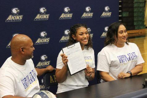 Making history- Senior Shanti Ramdeen (middle bottom), signs her letter of intent to play college volleyball at Coppin State University in Maryland. Ramdeen will be the very first volleyball athlete from Akins to attend a NCAA Division I school on an athletic scholarship. Her family, friends and  teammates celebrated  her accomplishment with her in a ceremony held in the Akins gym on Nov. 11. Two of her middle school volleyball coaches also attended the event.
