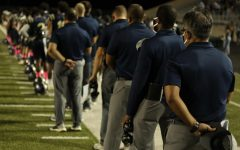 Looking towards the future- Head Coach Humberto, Garza  (middle right) pauses for anthem with students and coaches at Akin's first homecoming game against Del Valle.
