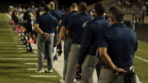 Looking towards the future- Head Coach Humberto, Garza  (middle right) pauses for anthem with students and coaches at Akins first homecoming game against Del Valle.