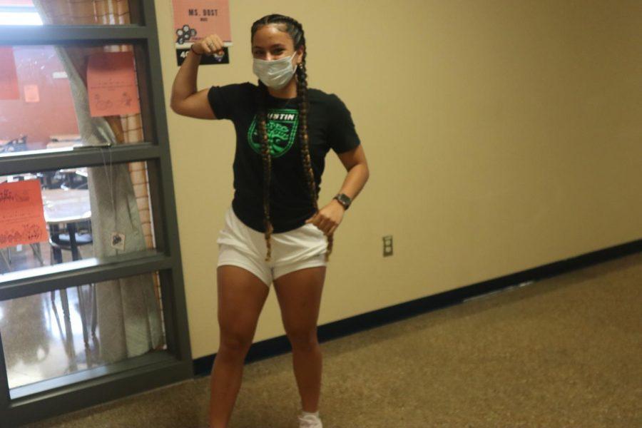 Senior Ana Claudia flexing in the STEM hallway.