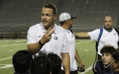 Coach Joey Saxe talks to players after Homecoming win against the Austin High Maroons