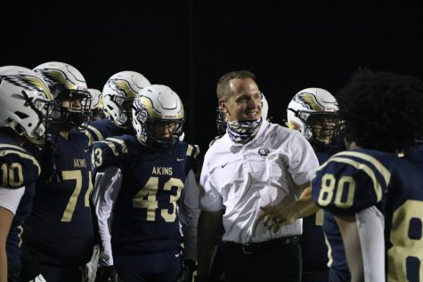 Coach Saxe with football players during the Homecoming game.