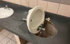 A detached sink lies on the counter in a boys bathroom after being disconnected in an effort to damage the bathroom as part of the Devious Lick trend that spread on TikTok.